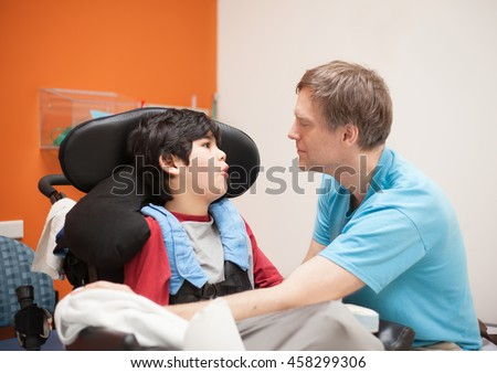 Father talking with disabled biracial son sitting in wheelchair while waiting in doctor's office.