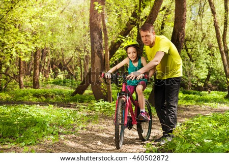 Father teaches daughter to ride bicycle outdoors
