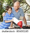 Father teaches his son how to put oil in the family car. - stock photo