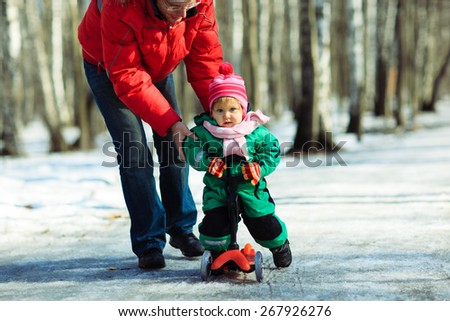 father teaches little daughter to ride scooter outdoors  - stock photo