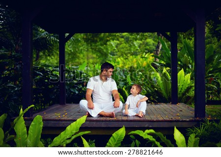 father teaches son to find inner balance - stock photo