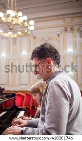 father teaches young daughter playing piano - stock photo