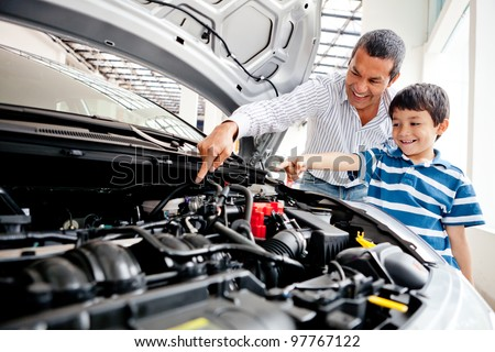 Father teaching car mechanics to his son and pointing the engine - stock photo