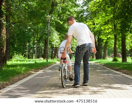 Father teaching cycling his little daughter in the summer park