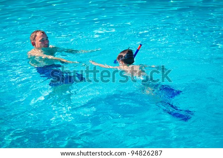 Father teaching his little son to swim under water surface in a swimming pool - stock photo