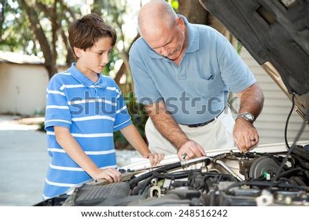 Father teaching his son basic auto maintenance.   - stock photo