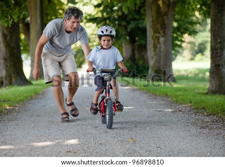 Father teaching his son to ride a bike - stock photo