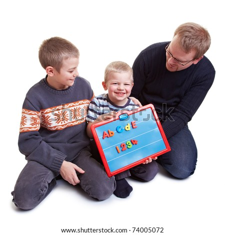 Father teaching his two boys with a magnetic board - stock photo