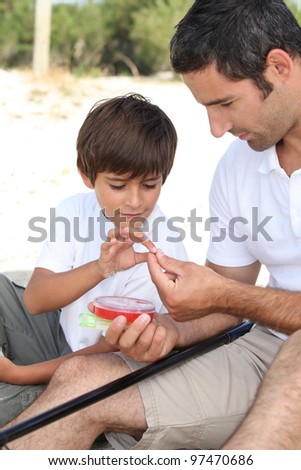 Father teaching his young son to fish - stock photo