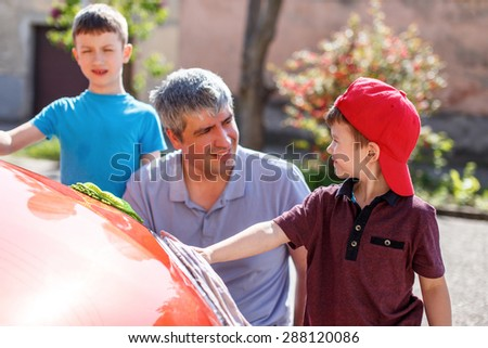 Father teaching son cleaning the spotlight, family car wash - stock photo