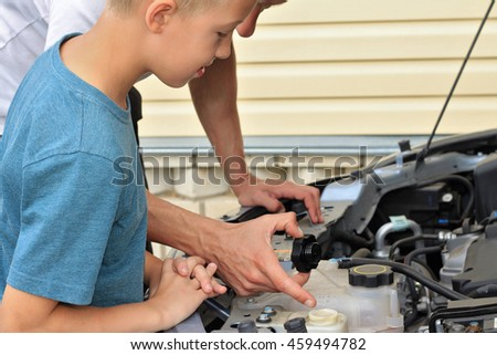 Father teaching son how to repair the car. Family concept