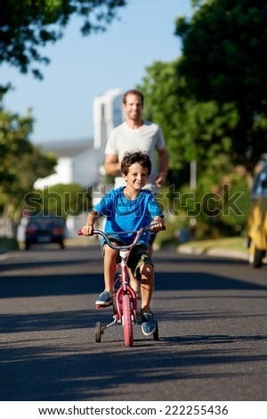 father teaching son learning to ride bicycle boy - stock photo
