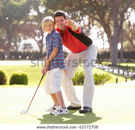 Father Teaching Son To Play Golf On Putting On Green - stock photo