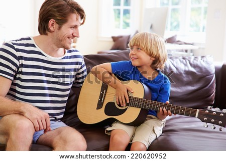 Father Teaching Son To Play Guitar - stock photo