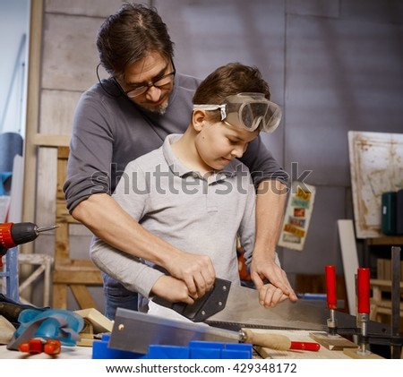 Father teaching son to use saw in workshop. - stock photo