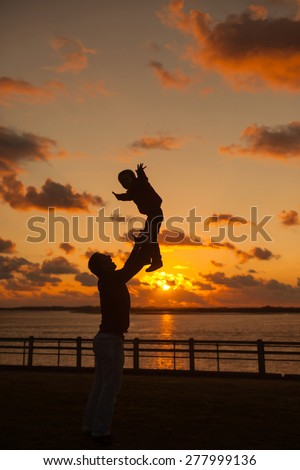 Father throwing his kid up in the air on the beach, silhouette shot on sunset. Father day concept - stock photo