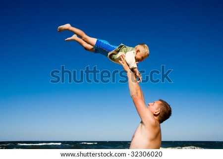 Father throwing his son high on a beach - stock photo