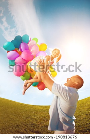 Father throws daughter. Family playing together in park with balloons. Father tosses a baby against the sky - stock photo