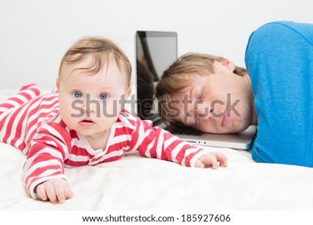 father tired of working from home- parent sleeping on laptop while baby crawling - stock photo