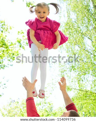 Father tossing up his daughter laughing in the park - stock photo