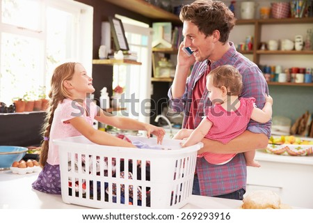 Father Using Mobile Phone As He Sorts Laundry With Children - stock photo