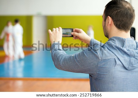 Father waiting for his kids training martial arts  - stock photo