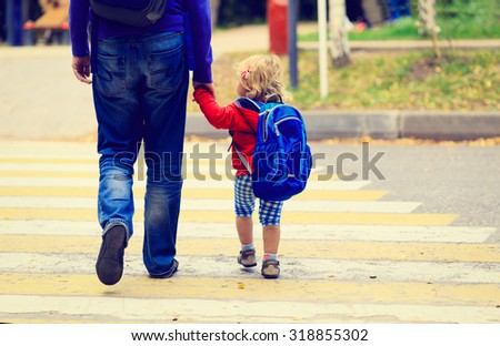 father walking little daughter with backpack to school or daycare - stock photo