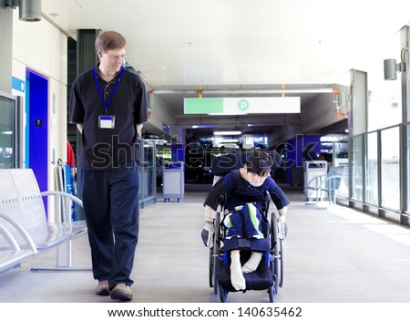 Father walking with disabled son in wheelchair as he wheels himself into the hospital entrance - stock photo