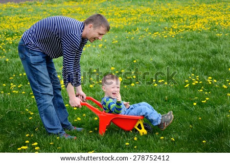 Father walking with his son on a flowering spring meadow. - stock photo