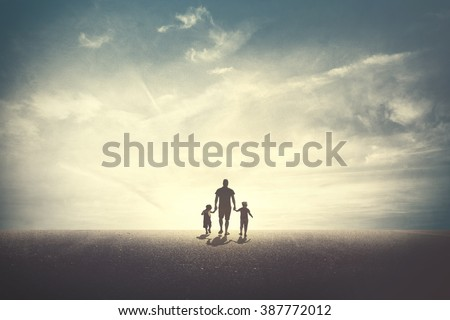 Father walking with his two daughters - stock photo