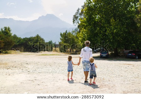 Father walking with two kids at the summer time - stock photo