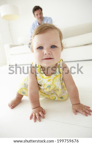 Father watching baby daughter crawl - stock photo