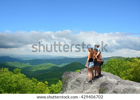 Father with arms around his family looking at beautiful summer mountains landscape. People standing on the top of the mountain. Blue sky in the background. North Carolina, USA. - stock photo