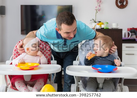 Father with baby boy and girl twins eating lunch on the high chair. - stock photo