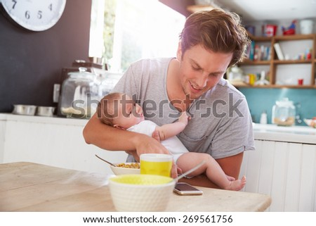 Father With Baby Daughter Checking Mobile Phone In Kitchen - stock photo