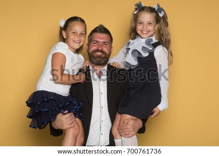 Father with beard and happy face holds schoolchildren. Schoolgirls with smiling faces. Education and school concept. Girls in school uniform on yellow background.