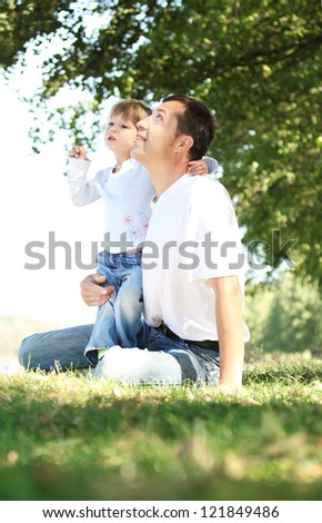 father with child playing on the grass - stock photo