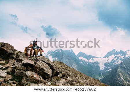 Father with child sitting on the top of the mountain, winter hike with backpacks, alpine view