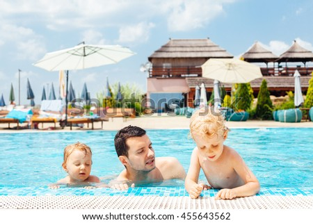 Father with children enters swimming pool - stock photo