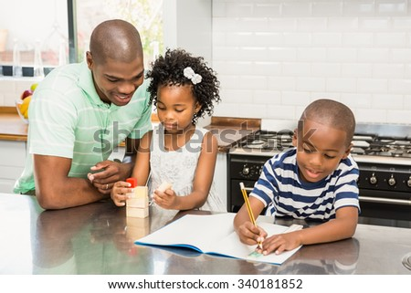Father with children in the kitchen at home - stock photo