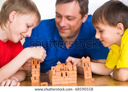 Father with children playing on the floor - stock photo