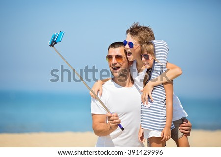 Father with children  taking selfie on the beach at the day time. - stock photo