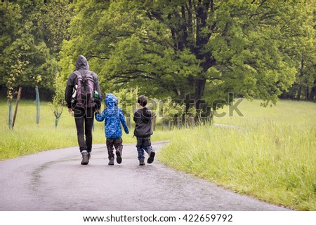 Father with children walking on countryside road on rainy day - stock photo