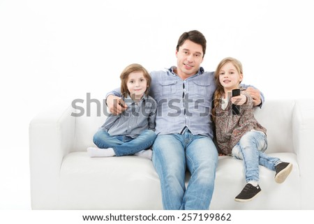 father with children watching television sitting on the couch on a white background