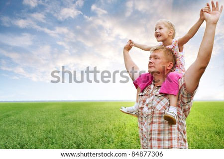 father with daughter in field hands up - stock photo