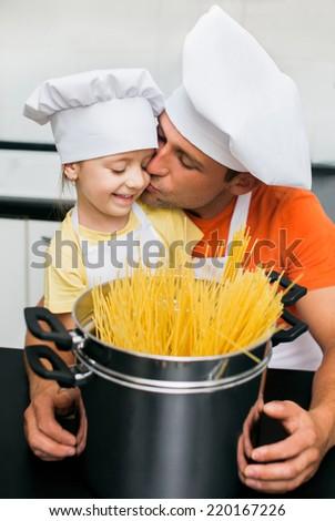 Father with daughter preparing spaghetti in kitchen - stock photo