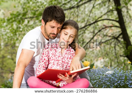 Father with daughter reading in the park outdoor - stock photo
