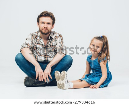 Father with daughter sitting on floor in jeans and plaid shirt