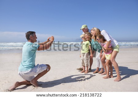 Father with digital camera photographing multi-generation family on sunny beach - stock photo