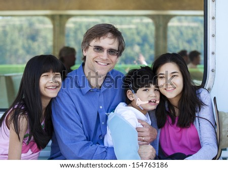 Father with his biracial children, holding disabled son on ferry boat deck. Boy has cerebral palsy - stock photo